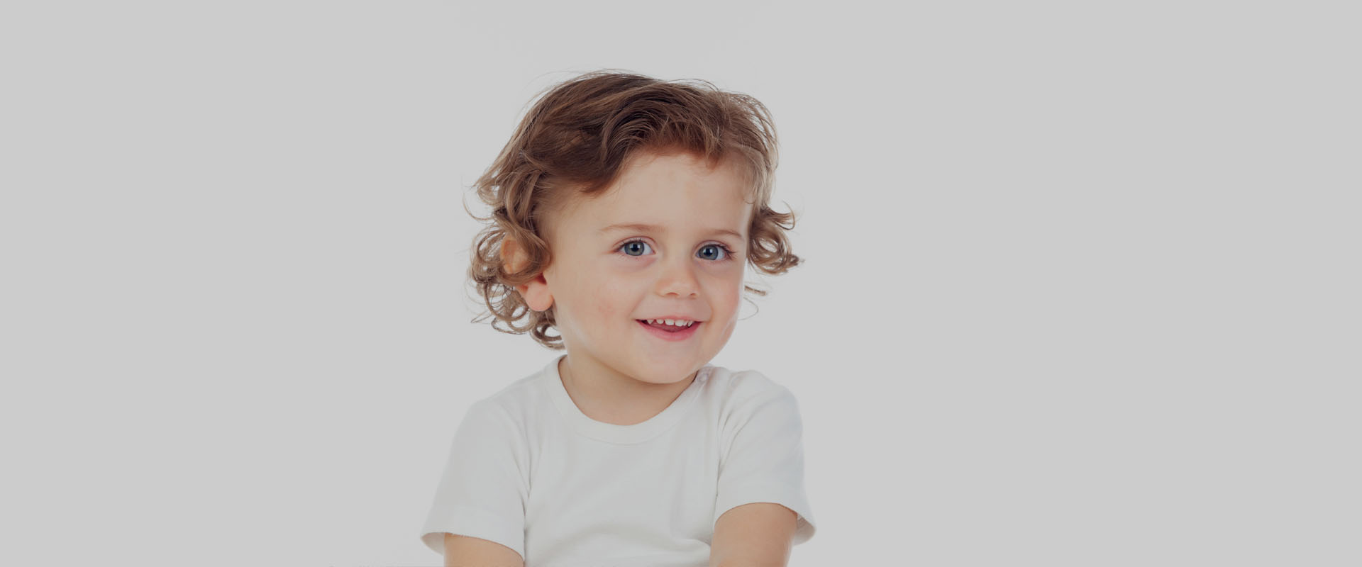 young toddler smiling showing baby teeth wearing white shirt